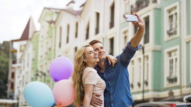 Young female and male in love hugging and taking selfie, romantic memories royalty free stock images