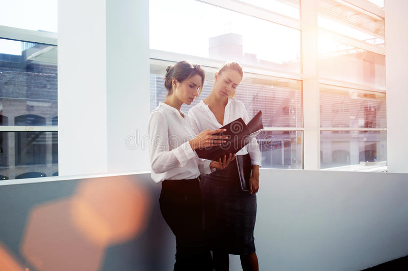 Young female manager consulting with colleague about presentation while holding folder documents. Successful women financiers discussing ideas of own project stock image