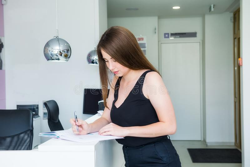 Young female manager standing at reception desk in office hall and plans working schedule, writes in notebook, makes notes of stock image