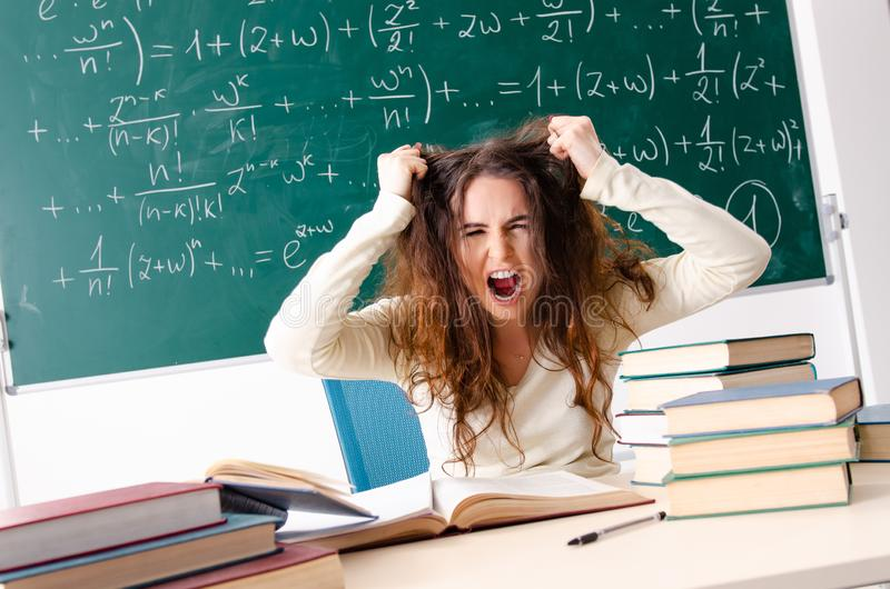 The young female math teacher in front of chalkboard stock photography