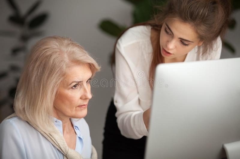 Young female mentor teaching senior woman colleague explaining c. Young mentor teaching senior colleague explaining computer work, corporate teacher training royalty free stock photography