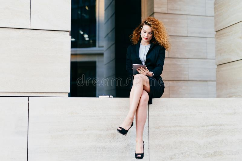 Young female model with curly hair, wearing elegant suit and high-heeled shoes, having slender legs, using modern tablet for commu royalty free stock photo