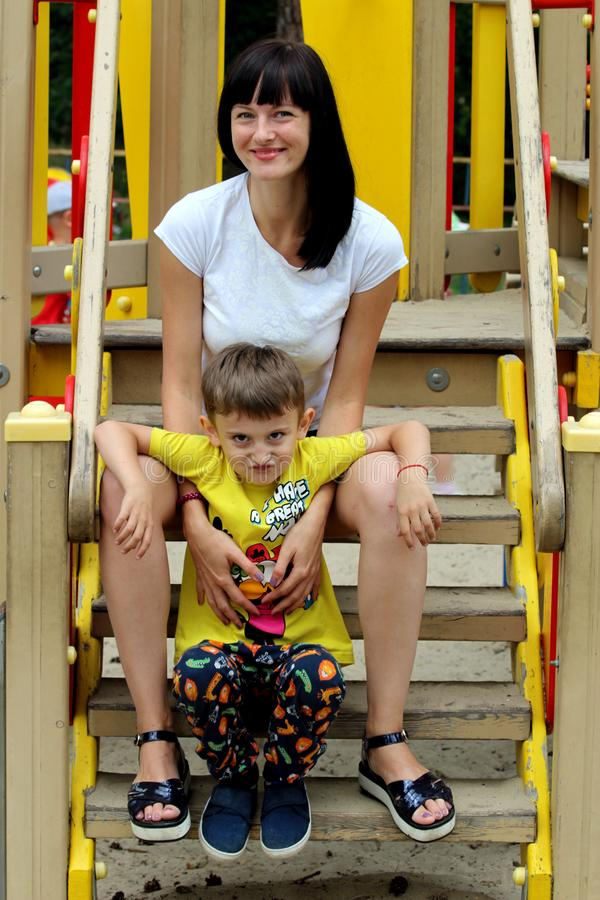 Young female model with dark hair looking at camera, resting in a park with her little son stock photos
