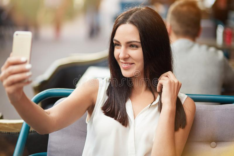 Young female model with dark straight hair and gentle smile poses for making selfie, sits against outdoor sidewalk cafe, uses mode. Rn smart phone. Positive stock image