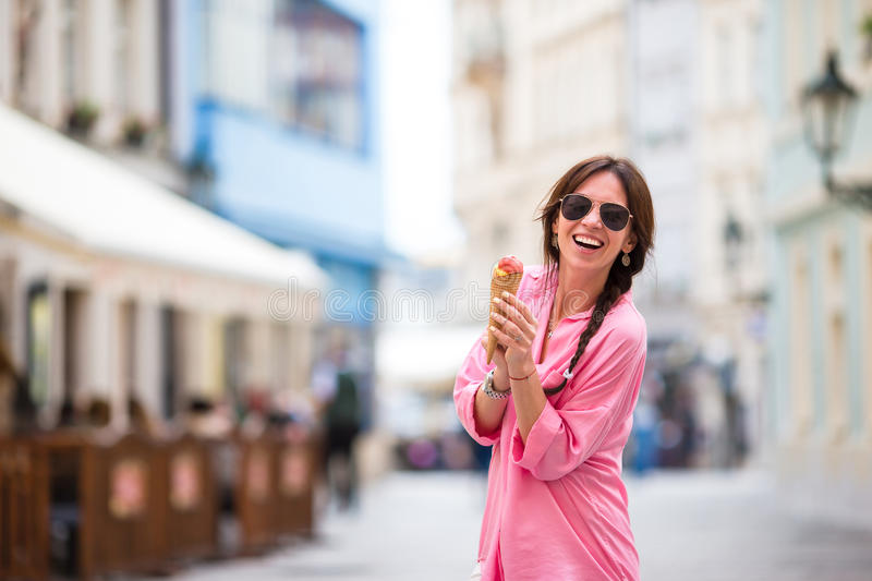 Young female model eating ice cream cone outdoors. Summer concept - woamn with sweet ice-cream at hot day royalty free stock photos