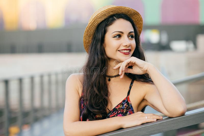 Young female model with long dark thick hair standing at bridge having dreamy expression looking into distance, wearing summer hat stock image