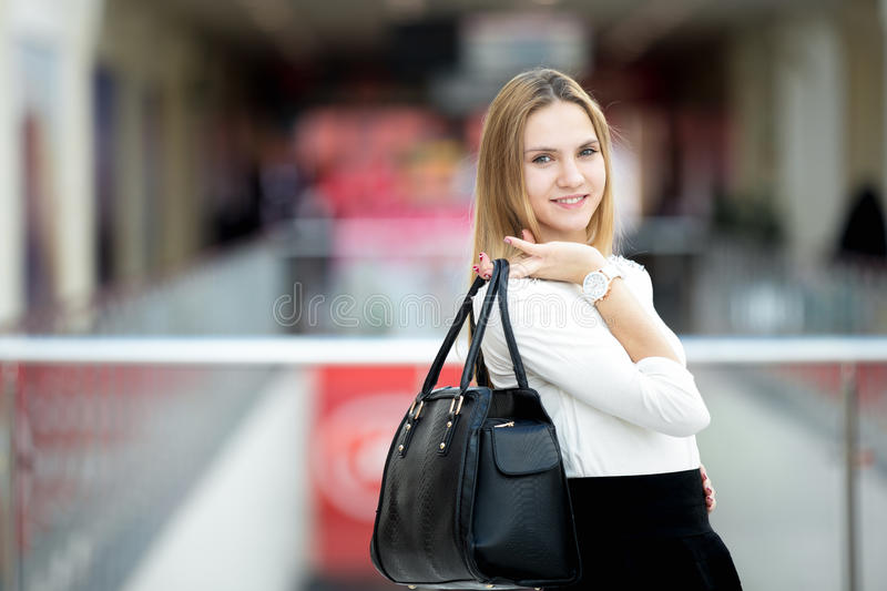 Young female model in stylish outfit holding handbag royalty free stock images