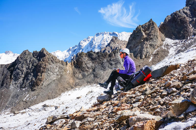 Young female mountaineer in a helmet resting sitting on a backpack and writes the passed route. Against the background of a chain of high rocky mountains and stock photo