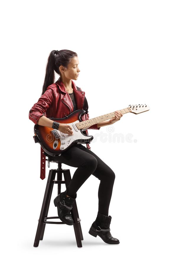 Young female musician sitting on a chair and playing electric guitar royalty free stock photo