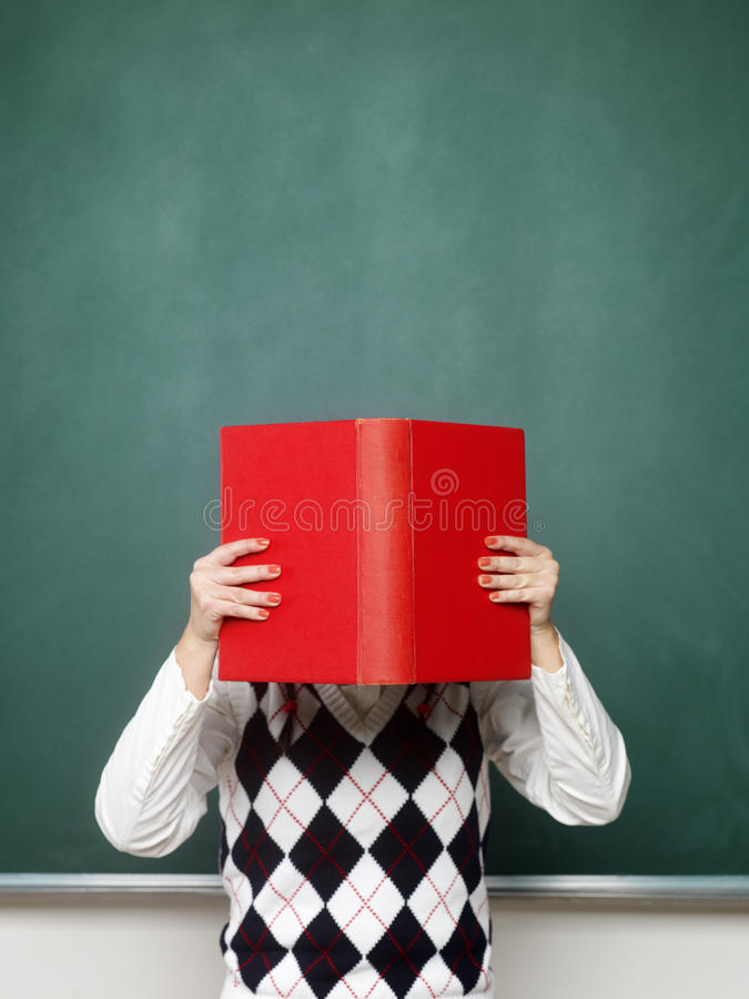 Young female nerd holding book royalty free stock photo