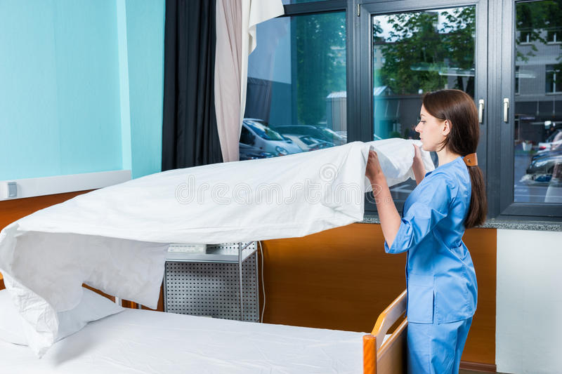 Young female nurse in blue unifrom changing bedsheets of hospital bed stock image