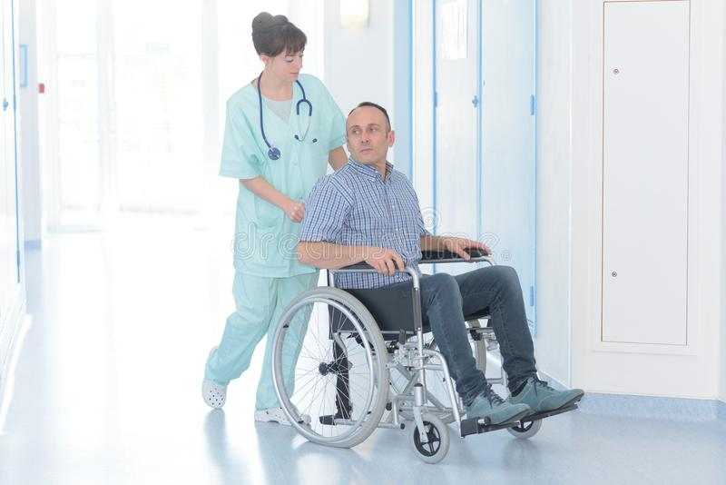 Young female nurse with disabled male patient on wheelchair stock photos