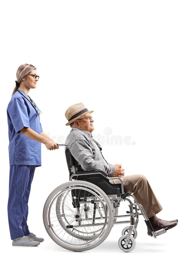 Young female nurse pushing an elderly gentleman in a wheelchair stock photography