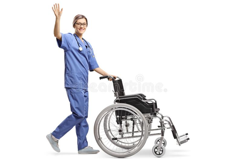 Young female nurse pushing an empty wheelchair and waving royalty free stock images