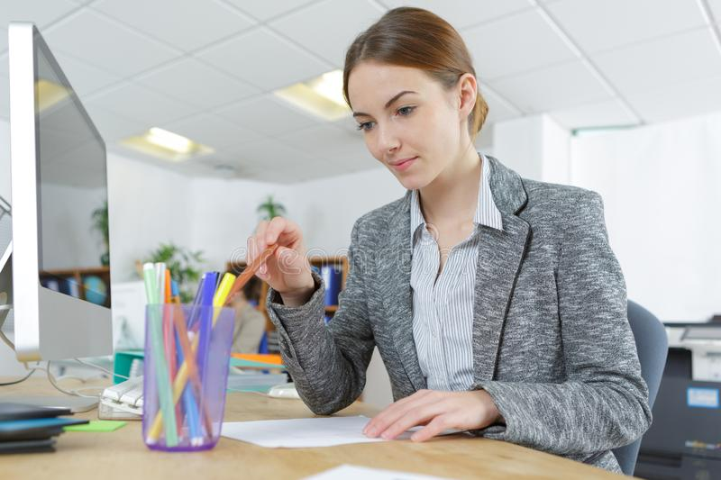 Young female office worker at computer desk sorting pencils. Female stock photo