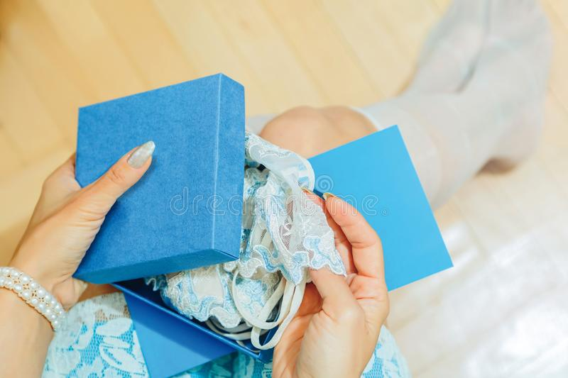 Young female opens a gift box with lingerie royalty free stock image