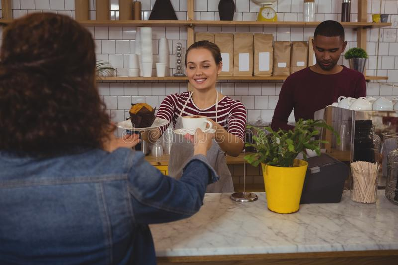 Female owner serving coffee and muffin to customer royalty free stock photo