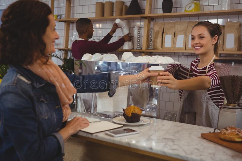 Female owner serving coffee to customer stock photo