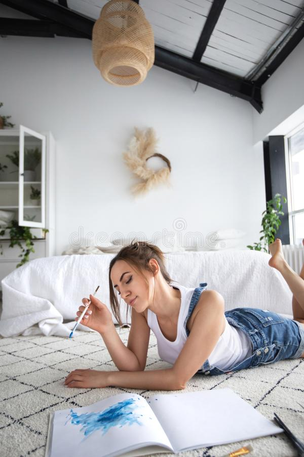 Young female painter painting picture on floor at home stock image