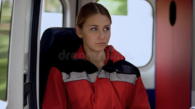 Young female paramedic sitting in ambulance, ready to drive out on call, 911. Stock photo stock image