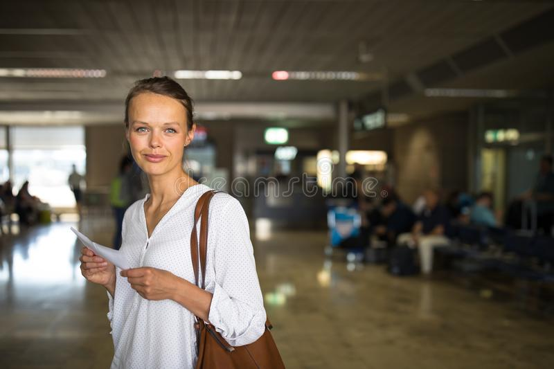Young female passenger at the airport. Waiting for her flight color toned image stock photo