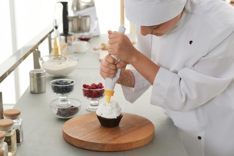 Young female pastry chef decorating cupcake with cream at table royalty free stock image