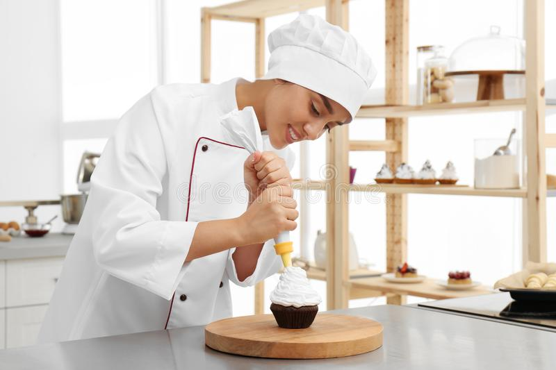 Young female pastry chef decorating cupcake with cream at table royalty free stock photo