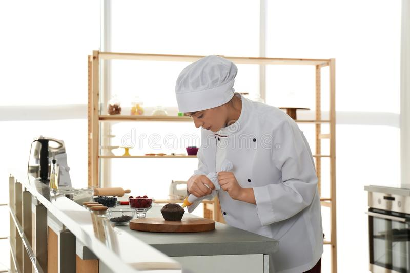 Young female pastry chef decorating cupcake with cream at table stock image