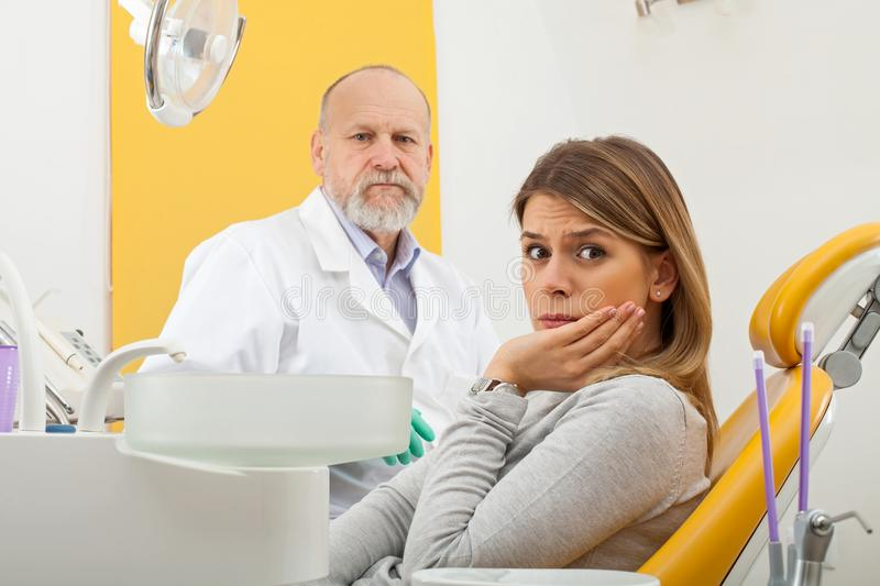 Female patient with toothache at the dentist office. Young female patient with severe toothache at the dentist office with elderly male dentist in the background royalty free stock images