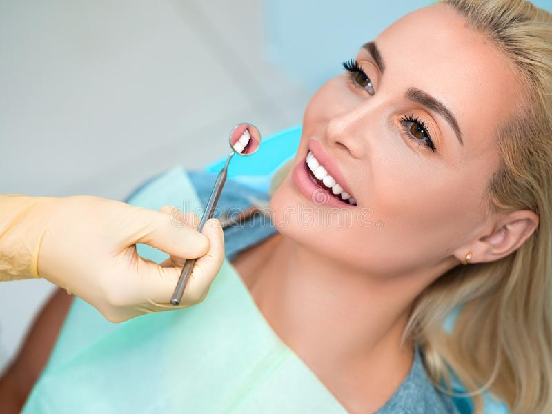 Young female patient visiting dentist office. Beautiful woman with healthy straight white teeth sitting at dental chair. royalty free stock photo