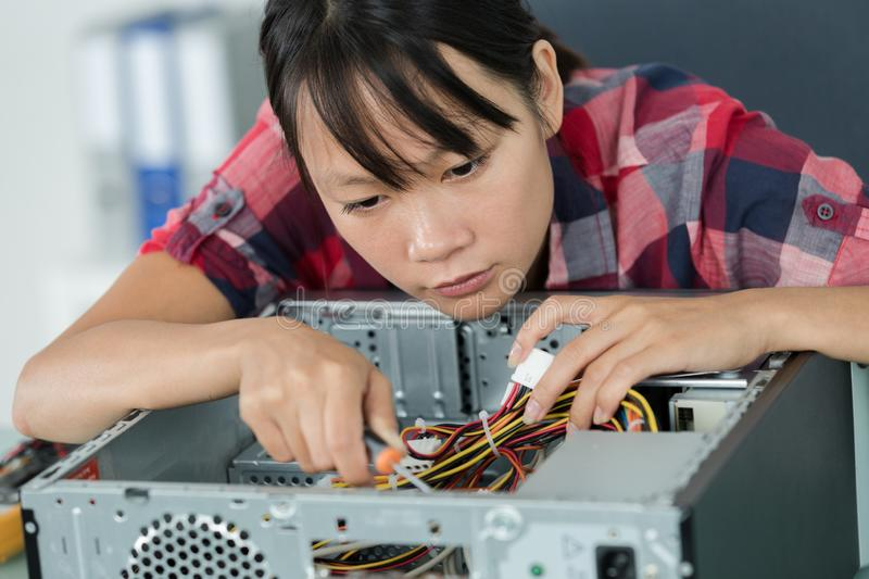 Young female pc technician in class stock photography