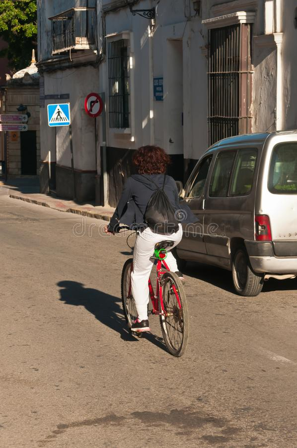 Young female peddling bike to work on vacant street in Spain stock photo
