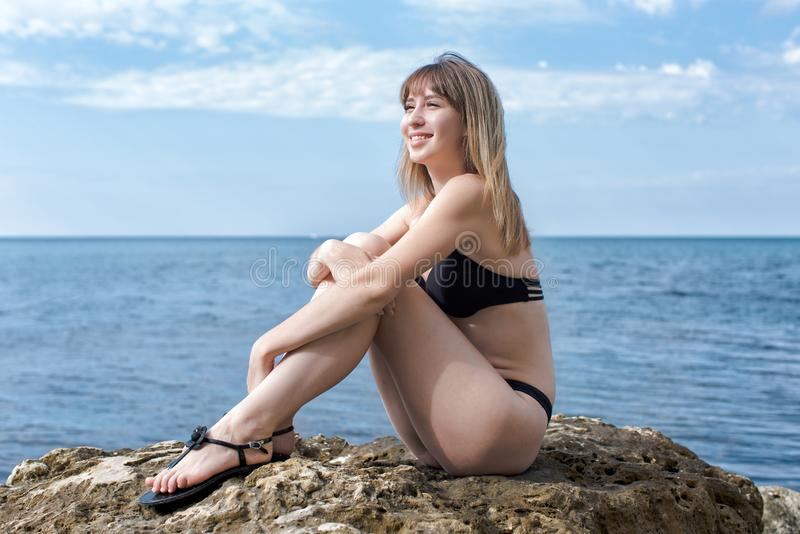 Young female person in bikini sitting on rock. Young woman sits with hands on knees on coastal boulder and smiling royalty free stock photography