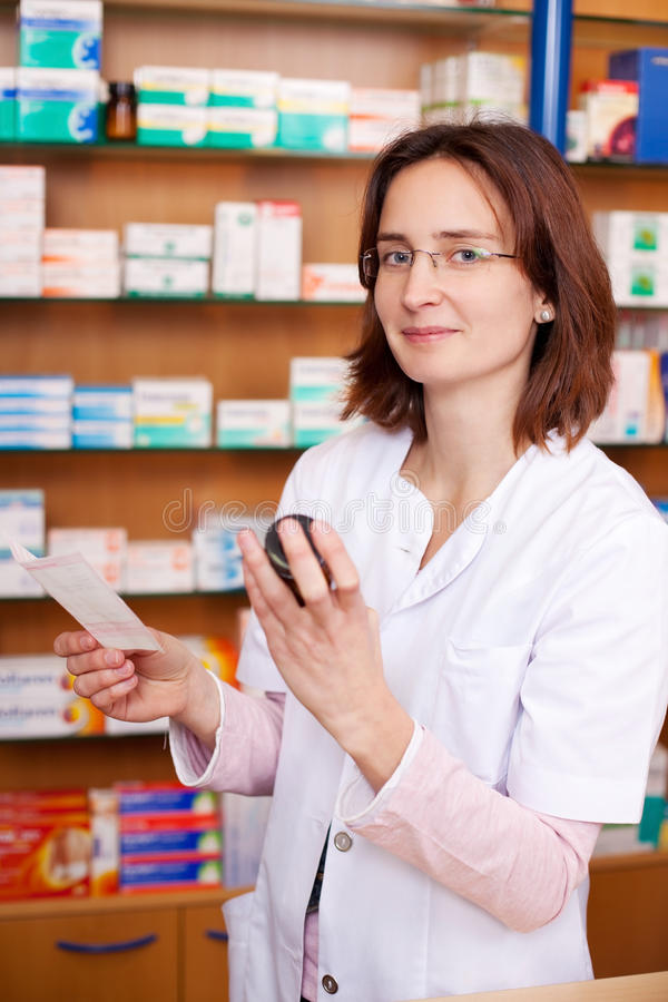 Young Female Pharmacist Holding Medicine Bottles royalty free stock images