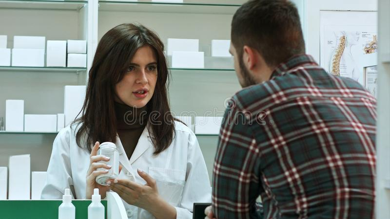 Young female pharmacist suggesting medical drug to male buyer in pharmacy drugstore royalty free stock photos