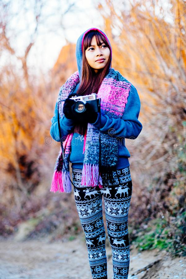 Young female photographer in cold weather wearing sweater and colorful scarf during afternoon sunset outside.  royalty free stock images
