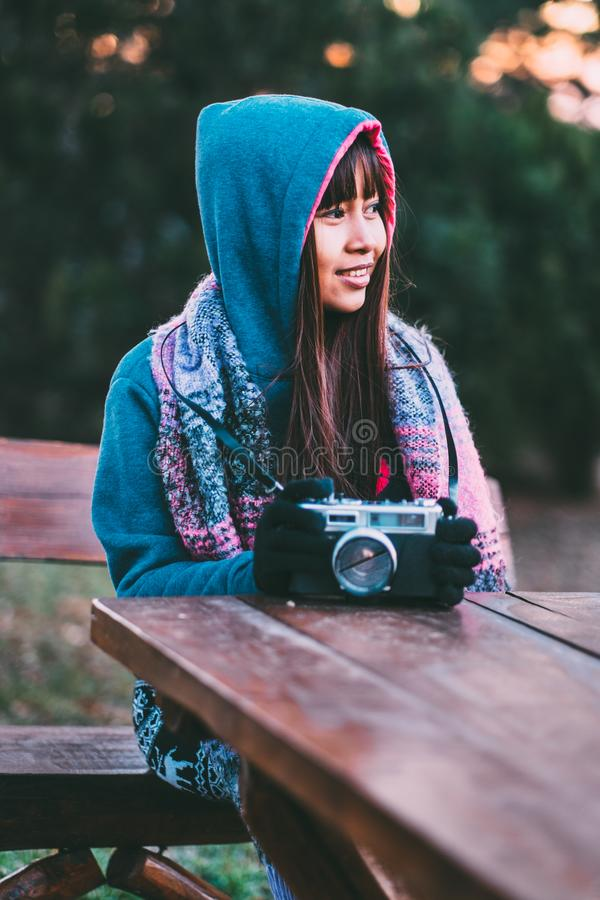 Young female photographer in cold weather wearing sweater and colorful scarf during afternoon sunset outside.  royalty free stock photo