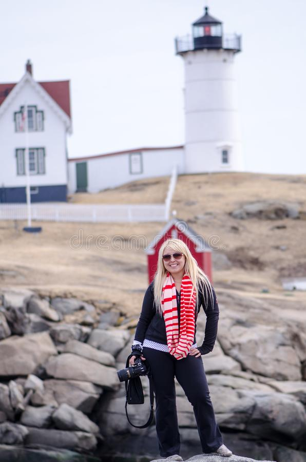 Young female photographer poses with her camera in front of Nubble Lighthouse in Maine royalty free stock photography