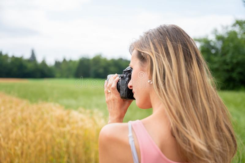 Young female photographer taking a photo of fields in nature royalty free stock image