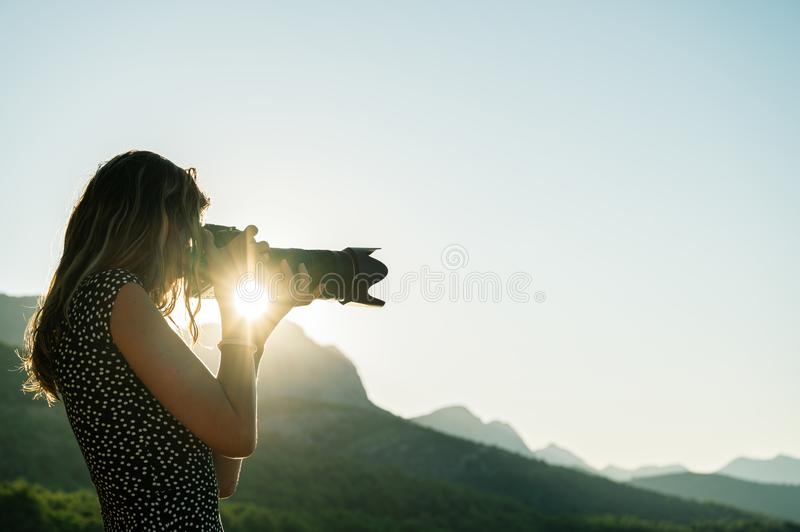 Young female photographer taking photos of beautiful nature royalty free stock photo