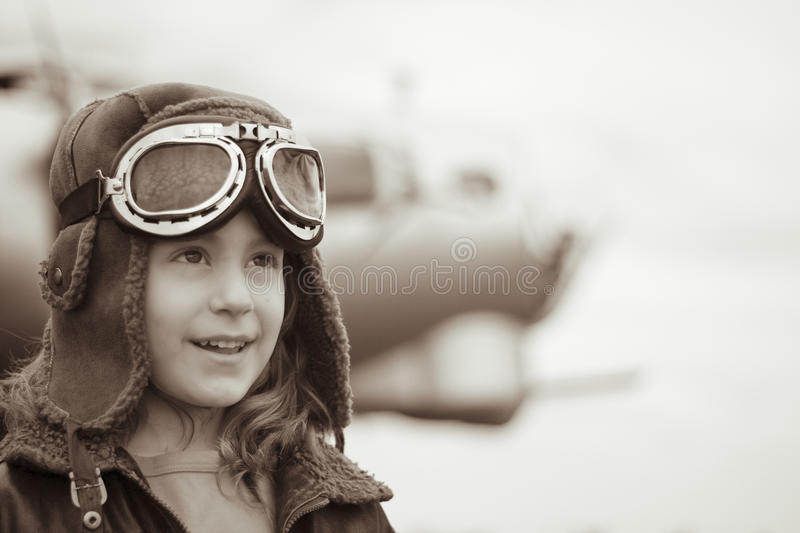 Young female pilot looking into distance. Young female pilot is looking off into the distance, wearing flight jacket/hat/goggles. Bomber is out of focus in the royalty free stock image