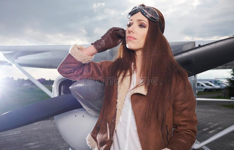 A young female pilot is standing next to a small training plane stock photos