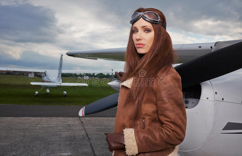 A young female pilot is standing next to a small training plane royalty free stock photo