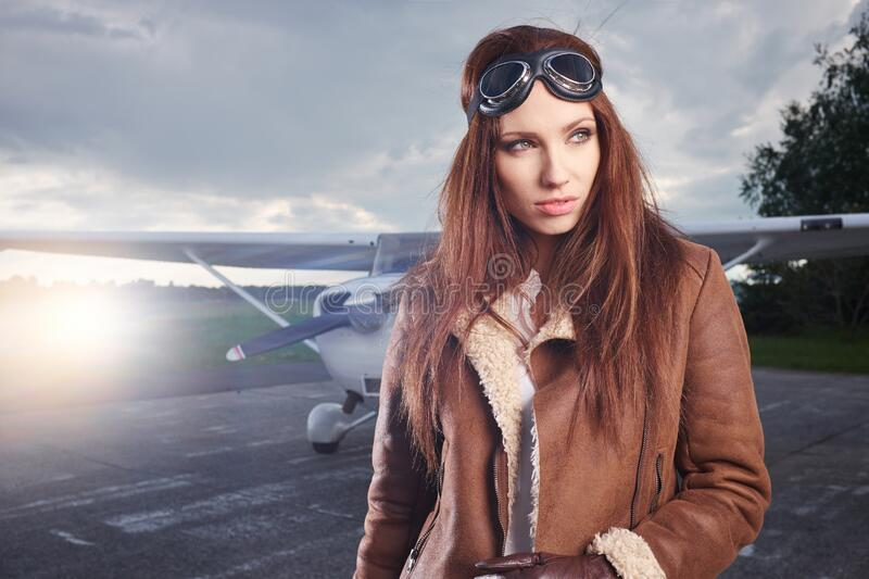 A young female pilot is standing next to a small training plane royalty free stock photography