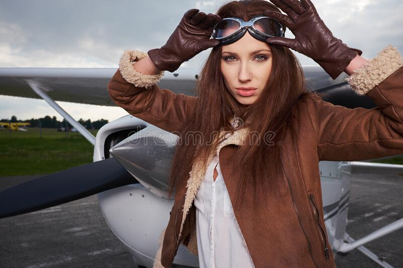 A young female pilot is standing next to a small training plane stock image