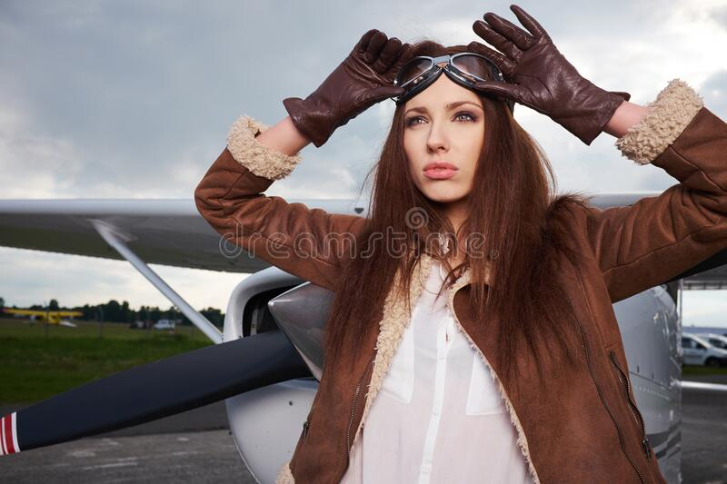 A young female pilot is standing next to a small training plane stock photo