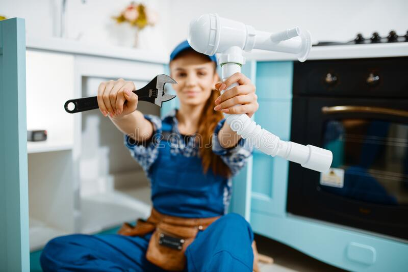 Young female plumber shows wrench and pipe stock image