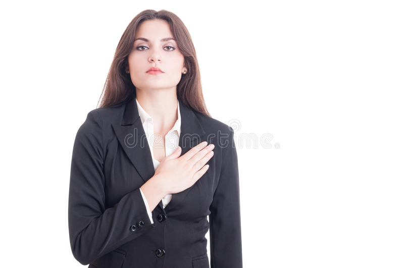 Young female politician or lawyer making an oath. With hand on heart and chest isolated on white background stock photo