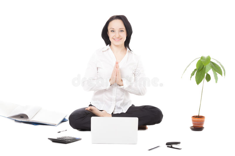 Young female professional resting in lotus pose in front of laptop on white background stock images
