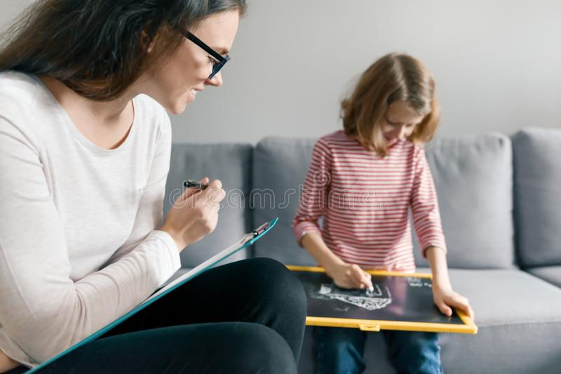 Young female psychologist talking with patient child girl in office. Mental health of children royalty free stock photography